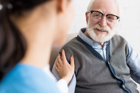 Selective focus of happy grey haired man looking at nurse