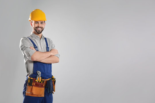 Portrait of professional construction worker with tool belt on grey background, space for text