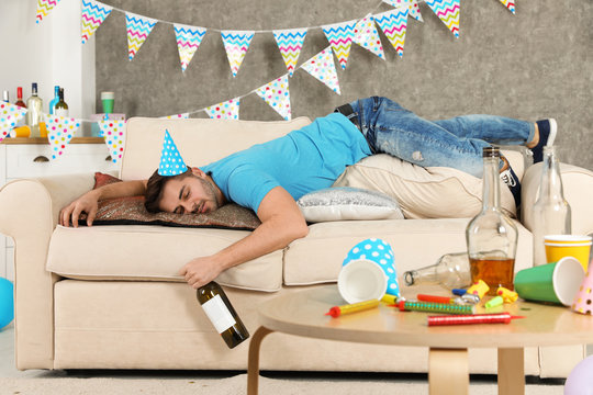 Young man with bottle of wine sleeping on sofa in messy room after party