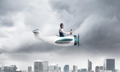 Businessman in aviator hat driving paper plane