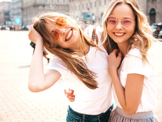 Portrait of two young beautiful blond smiling hipster girls in trendy summer white t-shirt clothes. Sexy carefree women posing on street background. Positive models having fun in sunglasses.Hugging Wall mural