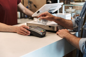 Cropped photo of caucasian man paying debit card in cafe while waiter holding payment terminal - fototapety na wymiar
