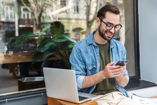 Photo of attractive young man holding smartphone while working on laptop in city cafe outdoors