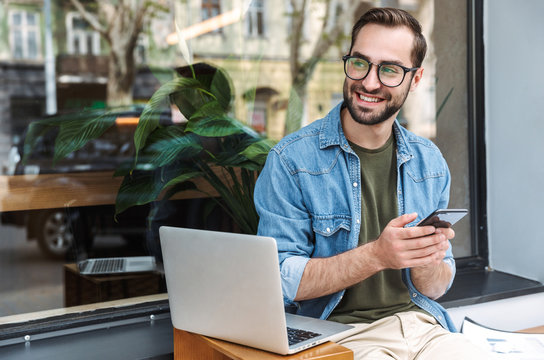 Photo of successful young man holding smartphone while working on laptop in city cafe outdoors