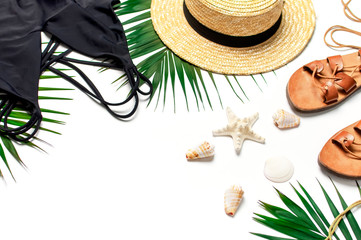 Woman's beach accessories flat lay. Round trendy rattan bag straw hat black swimsuit leather sandals tropical palm leaves seashells on white background. Top view copy space. Summer backdrop