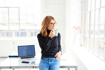 Beautiful businesswoman standing in the office while drinking her coffee