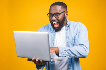 Young surprised african american man standing and using laptop computer isolated over yellow background.