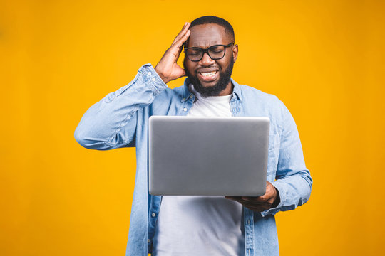 People and tiredness concept. Fatigue black African American man takes off spectacles, feels sleepy and overworked, surrounded with modern technologies.