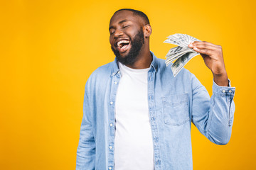 Winner! Young rich african american man in casual t-shirt holding money dollar bills with surprise isolated over yellow wall.