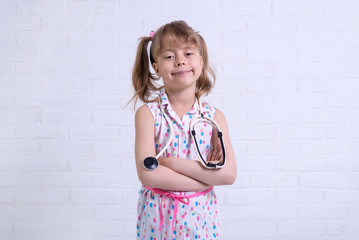 Portrait of a girl of about 7 years old with a stethoscope against a white wall, free space for your text.
