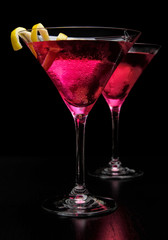 Pink cosmopolitan cocktails isolated on black