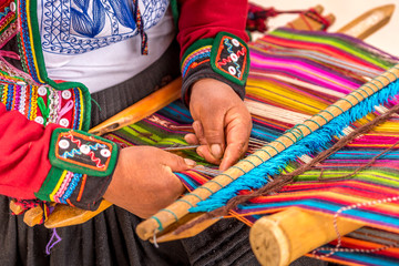 Peruvian woman working on traditional handmade wool production Wall mural
