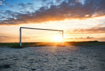 Soccer Goal on the Beach in Sundown Backlit with dramatic Clouds