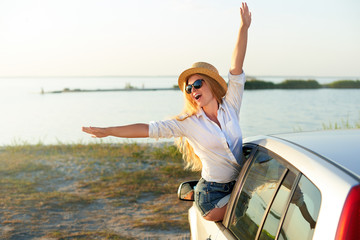 Pretty woman in straw hat enjoying road trip on a summer holidays. Excited young female raising her hands of the car window. Girl riding sitting on car door and leaning out of window arrived at beach. Fototapete