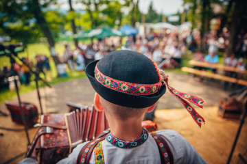 Young man playing on accordion in Slovak folk dress and folk hat. In front of the crowd
