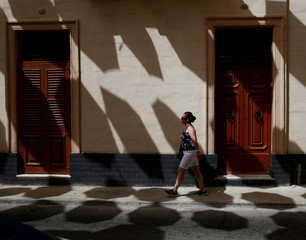 A woman walks through shadows cast by a canopy of coloured umbrellas hanging over a street in Zabbar