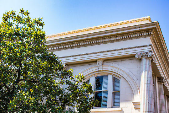 A Magnolia Tree Growing in front of a Traditional Cream Colored Building with Beautiful Columns in the French Quarter of New Orleans, Louisiana, USA