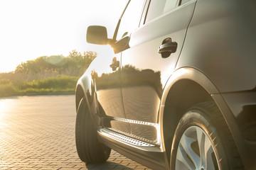Black SUV car in summer sunset