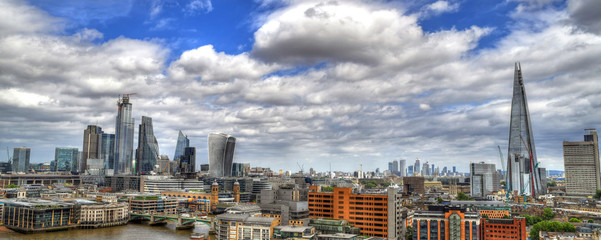 London skyline - old vs. new - skyscrapers and modern towers along with old European houses on blue cloudy sky - panoramic image