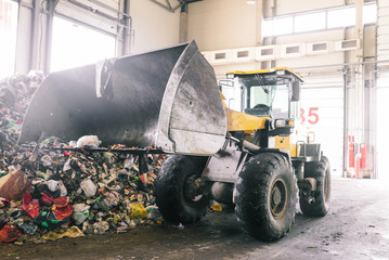 Hangar automated plant for sorting household waste. An excavator with a raised bucket collects and transports trash for recycling. Sorting and recycling