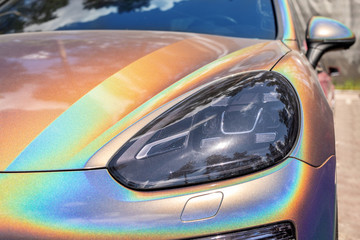 Close-up LED headlight expensive car part with exclusive iridescent painting. Vehicle covered with vibrant chameleon film