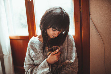 young serious brunette woman holding a tabby kitten