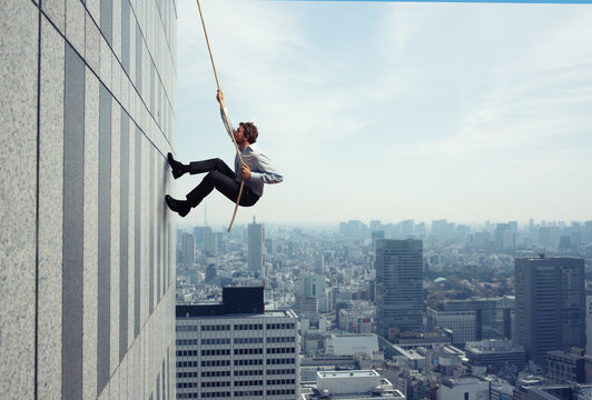Businessman climbs a building with a rope. Concept of determination