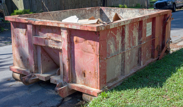 Battered red industrial dumpster parked on neighborhood street.