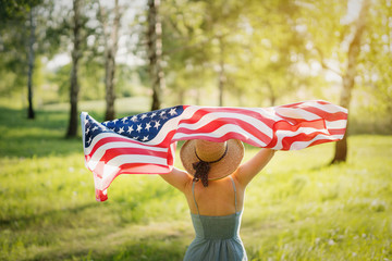 Closeup back view of a Proud woman enjoying summer sunset outdoors and holding american flag.