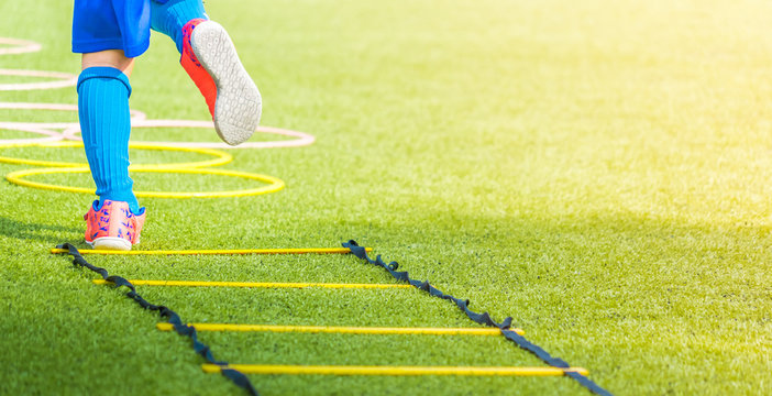 Child feet with soccer boots training on agility speed ladder in soccer training.
