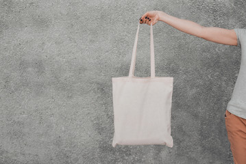 White cotton bag in woman's hand on grey background. Mock up.