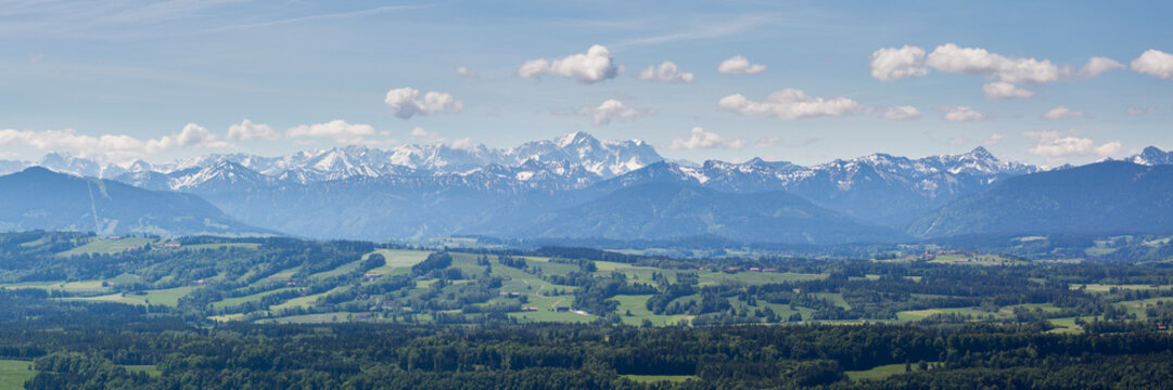 PEISSENBERG, BAVARIA / GERMANY - June 1, 2019: Huge panorama view of the Wetterstein Mountain Range (part of the alps). Blue sky and white clouds. Bavarian forests in the foreground.