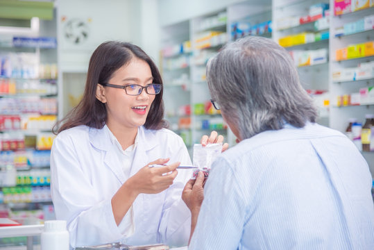Beautiful asian Pharmacist explaining the pills to patient in drug store