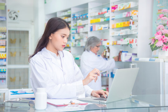Attractive young female pharmacist checking stock at the drugstore on computer notebook
