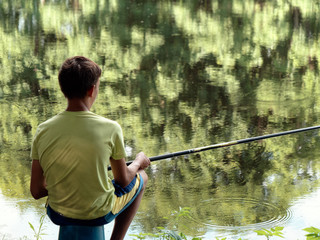 teen child catches a fishing rod on the pond.