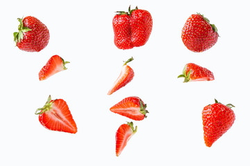 pieces and whole strawberries isolated on a white background in a chaotic manner . Fototapete
