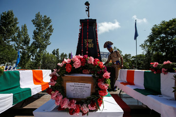 An Indian Central Reserve Police Force (CRPF) personnel stands behind the coffins of his colleagues during a wreath laying ceremony in Humhama