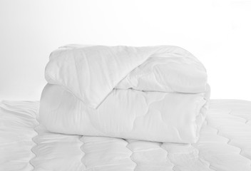 Rolled white soft duvet on the bed against the white background