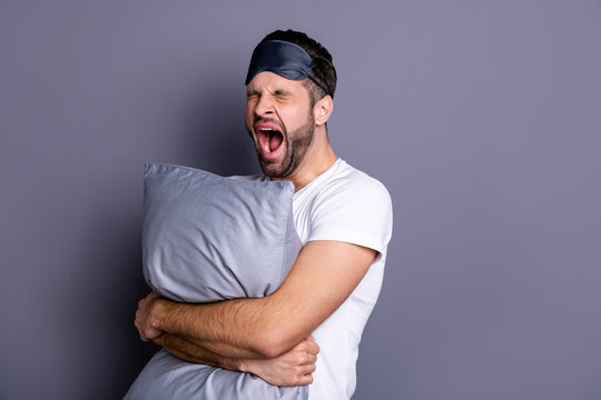 Portrait of his he nice-looking attractive exhausted sleepy bearded guy holding in hands pillow drowsiness going to bed isolated over gray pastel violet purple background