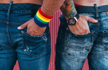 Full length back view of stylish gay couple posing hand in ass along sunny sidewalk.