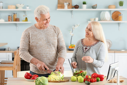 Portrait of happy mature couple cooking in kitchen