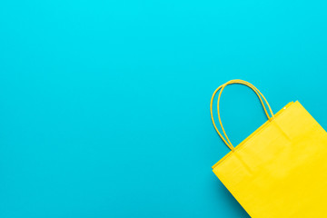 shopping paper bag on the turquoise blue background. flat lay photo of yellow bag. summer sale concept with copy space.