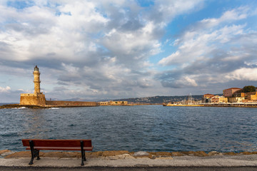 Lonely wooden bench on the waterfront of the Greek city of Chania against the background of the lighthouse