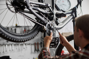 Cropped shot back view of male mechanic making service in bicycle repair shop, professional technician repairing modern bike using special tool, wearing protective workwear Fototapete