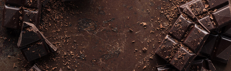 Panoramic shot dark chocolate bar with chocolate chips on metal background