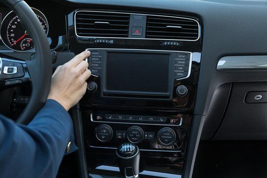 Business Frau bedient Autoradio in Mittelkonsole von Mittelklasse-PKW