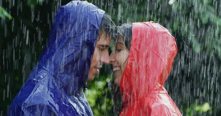 Portrait of young carefree couple in love are wearing protection capes hugging and kissing under the rain on a background of green trees.
