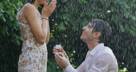 Portrait of young handsome man is making a proposal of marriage to his fiancee under the rain on a background of green trees.