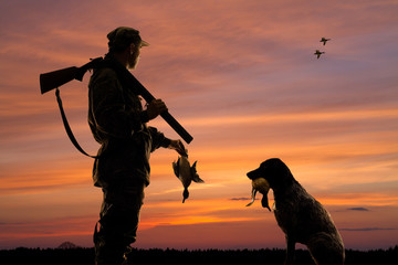 Fototapeta hunter and his dog with downed duck at sunset