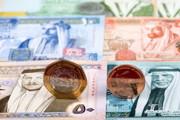 Jordanian Dinar coins on the background of banknotes